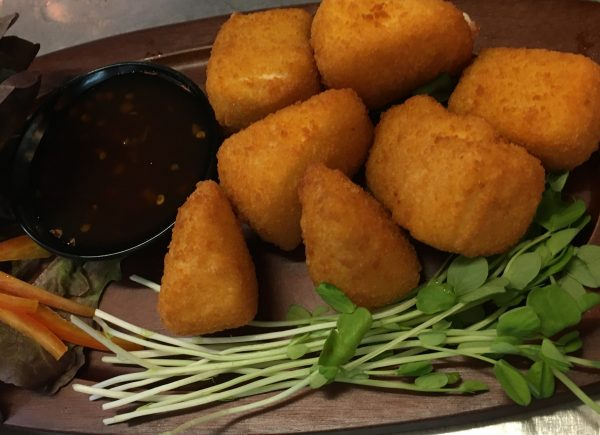 Crumbed camembert with dipping sauce and salad on wooden plate